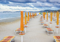 Rows of closed umbrellas and deckchairs on the empty beach Royalty Free Stock Photos