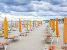 Rows of closed umbrellas and deckchairs on the empty beach Royalty Free Stock Images