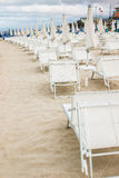 Rows of closed umbrellas and deckchairs on the empty beach Stock Images