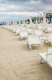 Rows of closed umbrellas and deckchairs on the empty beach Stock Photo