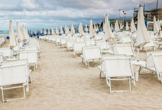 Rows of closed umbrellas and deckchairs on the empty beach Royalty Free Stock Image