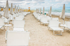 Rows of closed umbrellas and deckchairs on the empty beach Royalty Free Stock Photo