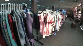 Rows with clothes on hangers hang in the second hand shop. View inside the shopping center. Kamenskoye, Ukraine, April 22, 2018: Rows with clothes on hangers stock footage