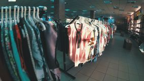 Rows with clothes on hangers hang in the second hand shop. View inside the shopping center. Kamenskoye, Ukraine, April 22, 2018: Rows with clothes on hangers stock video