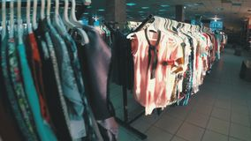 Rows with clothes on hangers hang in the second hand shop. View inside the shopping center. Second-hand clothes stock footage
