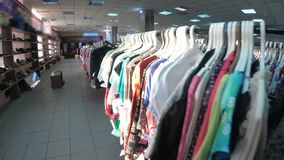 Rows with clothes on hangers hang in the second hand shop. View inside the shopping center. Second-hand clothes stock video footage