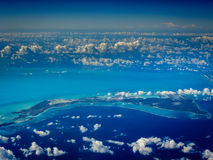 Rows of clouds dot an aerial view of Caribbean islands. Rows of clouds above blue coral reefs line up in aerial view of Caribbean islands and coral reefs stock photo