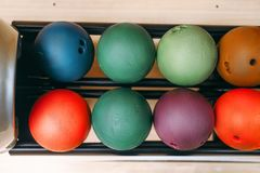 Rows of color bowling balls in feeder, top view royalty free stock images