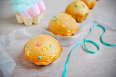 Freshly baked muffins with candy sprinkles on white wooden background royalty free stock photos