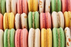 Rows of colorful french macarons - green, yellow and pink. Creative background royalty free stock images