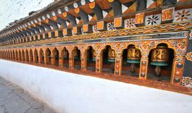 Rows of colorful religious prayer wheels in Paro Rinpung Dzong. Buddhist monastery and fortress at Paro, Bhutan Stock Photography