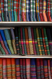 Rows of colorful traditional strip and checker pattern fabric textile rolls on shelves in local shop Royalty Free Stock Images