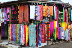 Rows of colourful silk scarfs hanging at a market stall in Indon Stock Image