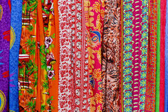 Rows of colourful silk scarfs hanging at a market stall in Thail Stock Images