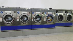 Rows of commercial industrial washing machines at laundromat / laundrette for public / consumer`s use. Rows of different sizes commercial industrial washing stock photo