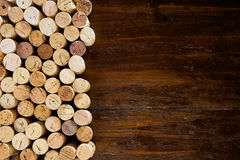 Rows of corks on a wooden background. Rows of corks forming a side border on an old wooden background in a full frame view with copy space Royalty Free Stock Photo
