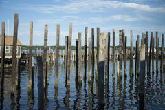 Rows of Dock Piles in Blue Water against Blue Cloudy Sky. An unending line of dock piles and a dockhouse in the blue water reflecting the blue sky with clouds Stock Image