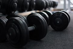Rows of dumbbells in the gym in the dark colors. Rows of dumbbells at the gym. Dumbbells lie on the floor. Dark colors Stock Photos