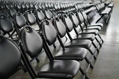 Rows of empty black folding chairs. View of rows of empty black folding chairs at an event Stock Photography