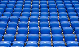 Rows of blue plastic armchairs on a tribune of stadium. Rows of empty blue plastic chairs on a tribune of stadium going to perspective Royalty Free Stock Photos