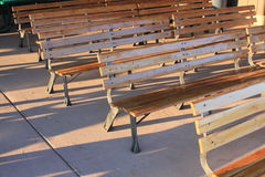 Rows of empty brown wooden benches Royalty Free Stock Image