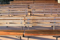 Rows of empty brown wooden benches Stock Image