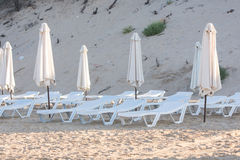 Rows of empty chairs on beach with a deflated parasols Royalty Free Stock Image