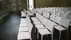 Rows of empty chairs. Rows of white empty Charis ready for a public seminar, coaching seminar, public lesson, training event stock video