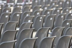 Rows of empty dark chairs. Abstract. Back view. Mid shot royalty free stock image