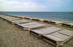 Rows of empty deckchairs on the empty pebble beach Royalty Free Stock Image