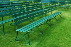 Rows of empty green outdoor benches on grass. Rows of empty green outdoor bench seating on grass with nobody Stock Images