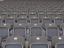 Rows of empty grey seats in an arena or stadium Stock Images