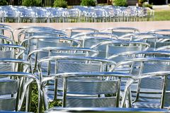 Rows of empty metal chair seats installed for some business event or performance,festival.Many empty parallel arranged. Rows of empty metal chair seats installed royalty free stock image