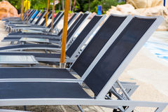 Rows of empty modern style beach pool recliner chairs Stock Photo