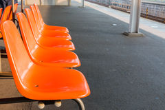 Rows of an empty orange plastic seats in railway station. Stock Image