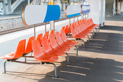 Rows of an empty orange plastic seats in railway station. Royalty Free Stock Image