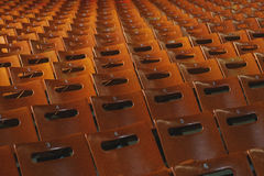 Rows of empty orange seats in the stadium. Places for the spectators. Stock Photo