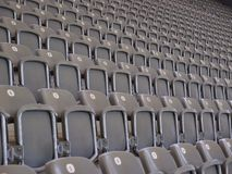 Rows of empty seating in an auditorium or arena. Rows of tiered numbered empty grey seating in an auditorium, stadium or arena ready for an audience to attend an Royalty Free Stock Images