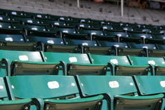 Rows of empty stadium seats. Several rows of empty green and gray stadium seats, some out in the elements while others are set under overhead protection stock image