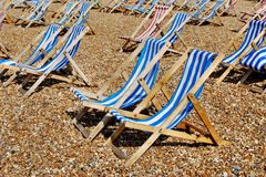 Rows of empty traditional deckchairs on beach. Rows of empty traditional seaside deckchairs on Brighton beach, England, UK Royalty Free Stock Photography