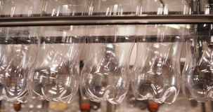 Rows of empty water bottles at bottling plant. In factory stock footage