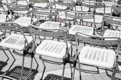 Rows of empty white metal chairs Stock Photos