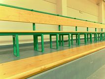 Rows of empty wooden benches in school sporting hall.  Tribune in gym for fans. Of matches with empty wooden seats Stock Photography
