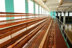 Rows of empty wooden benches in sporting hall. Tribune in gym for fans of matches with empty wooden seats Stock Photography
