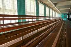 Rows of empty wooden benches in sporting hall. Tribune in gym for fans of matches with empty wooden seats Stock Photos