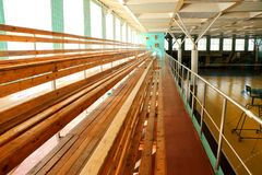 Rows of empty wooden benches in sporting hall. Tribune in gym for fans of matches with empty wooden seats Stock Image