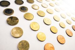 Rows of euro currency coins next to eachother. On a white background with bokeh Stock Photo