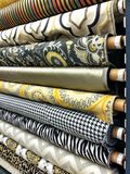 Rows of fabric bolts of material. Rows of material fabric bolts for sale in fabric store Stock Image