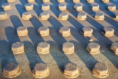 Rows of Fastened Bolts. Closeup on rows of bolts fastened to a metal plate outdoors. Horizontal shot Stock Photography
