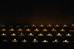 Rows of firing candles Royalty Free Stock Photography